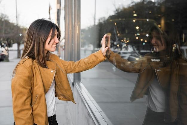 Señora joven sonriente con la mano en ventana de la tienda
