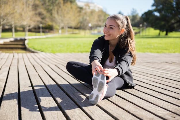 Señora joven sonriente que estira la pierna al aire libre