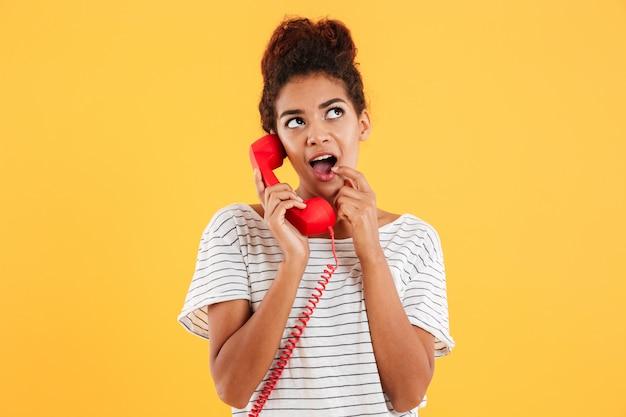 Señora joven sonriente que sostiene el microteléfono rojo aislado