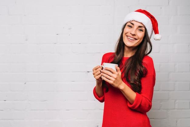 Señora joven sonriente en sombrero del partido con la taza