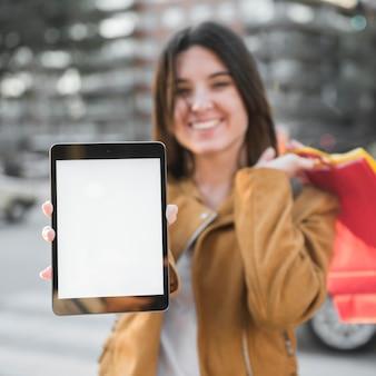 Señora joven sonriente con la tableta