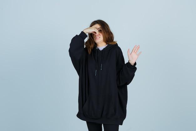 Señora joven con sudadera con capucha de gran tamaño, pantalones pellizcando la nariz debido al mal olor y mirando disgustado, vista frontal.