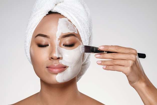 Señora joven con una toalla en la cabeza poner scrab en su rostro aislado