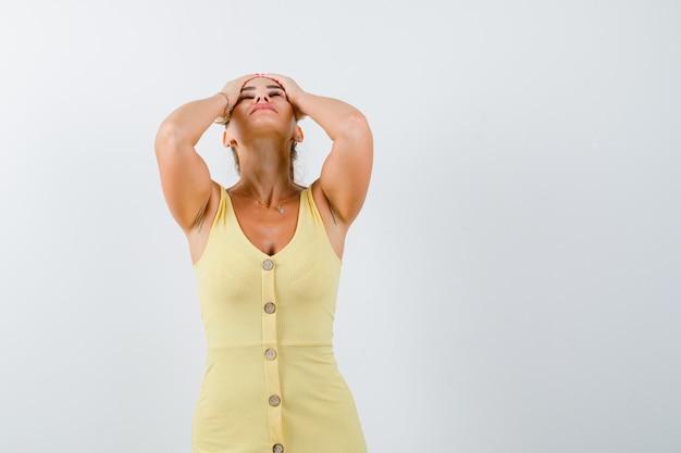 Señora joven en vestido amarillo cogidos de la mano en la cabeza y mirando exhausto, vista frontal.