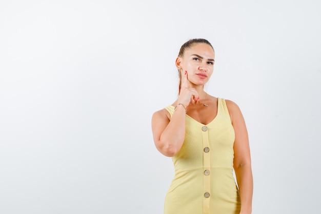 Señora joven en vestido amarillo sosteniendo el dedo en la mejilla, mirando hacia arriba y mirando pensativo, vista frontal.