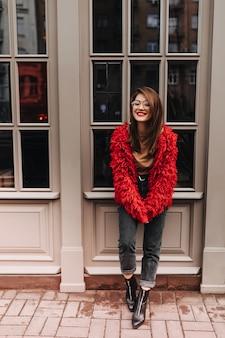 Señora con lápiz labial rojo en gafas, elegantes pantalones de mezclilla, abrigo brillante sonriendo y posando afuera junto a la ventana con marco blanco.