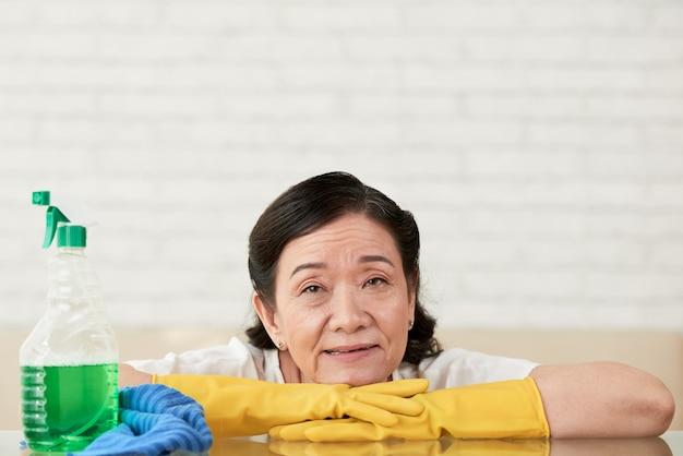 Señora de la limpieza apoyada en sus manos con guantes tomando un descanso de pulir la mesa