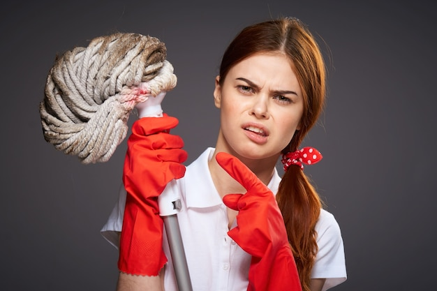 Señora de la limpieza sosteniendo una fregona.