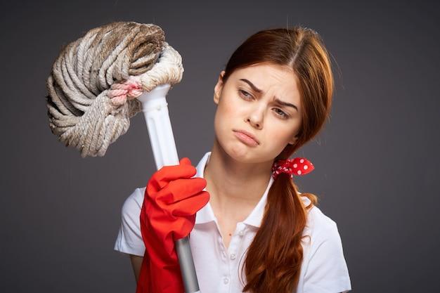 Señora de la limpieza trapeador con guantes de goma en las manos el trabajo de rutina del trabajo doméstico