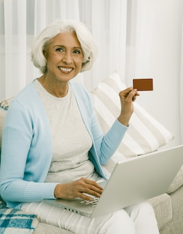 Señora madura alegre se ríe con tarjeta de crédito y computadora