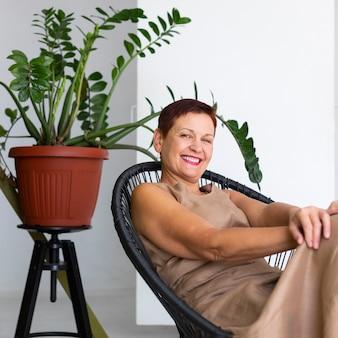 Señora madura sonriente con planta detrás