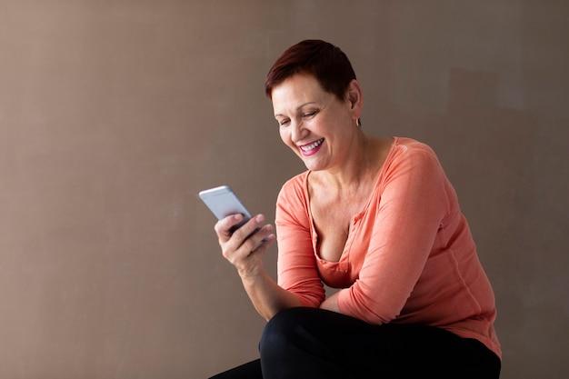 Señora madura sonriente con smartphone