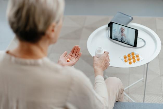 Señora madura tomando pastillas bajo la supervisión de un médico
