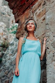 Señora magnífica que se inclina en la pared y que sonríe en vestido azul largo durante el día.