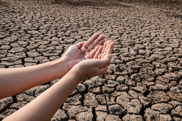 Señora mano esperando agua de lluvia, suelo agrietado y seco en zonas áridas paisaje