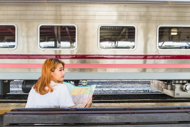 Señora con mapa en asiento cerca de tren en plataforma