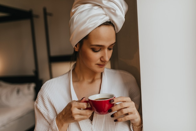 Señora sin maquillaje con una toalla en la cabeza sosteniendo una taza de café roja. mujer en bata de baño posando en el dormitorio.