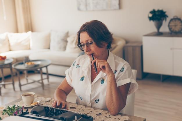 Señora mayor en camisa blanca mordiendo pluma y pensando en casa durante el día