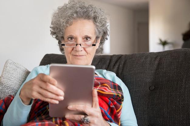 Señora mayor contenta con el pelo rizado que usa el dispositivo moderno en casa
