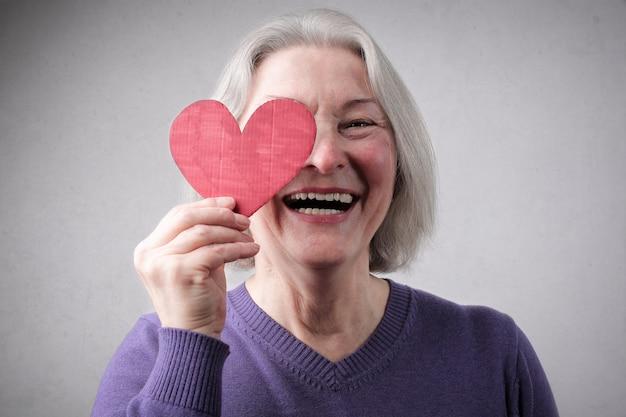 Señora mayor con un corazón rojo