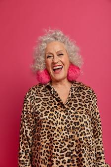 La señora mayor encantada del glamour se ríe felizmente, siendo entretenida por alguien, vestida con ropa de moda para una ocasión especial, aislada sobre fondo rosa. mujer madura en elegante traje de leopardo