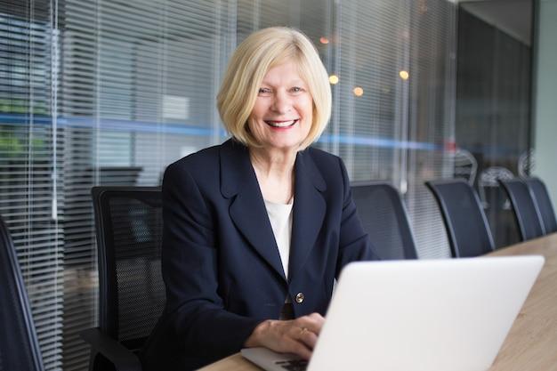Señora mayor feliz con el ordenador portátil en la sala de conferencias