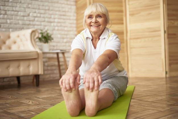 Señora mayor feliz touches toes workout en casa.