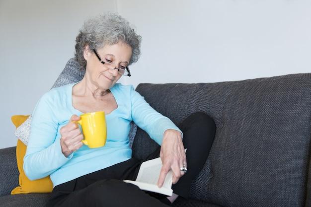 Señora mayor positiva que disfruta de la novela emocionante