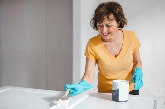 Señora mayor que pinta en casa