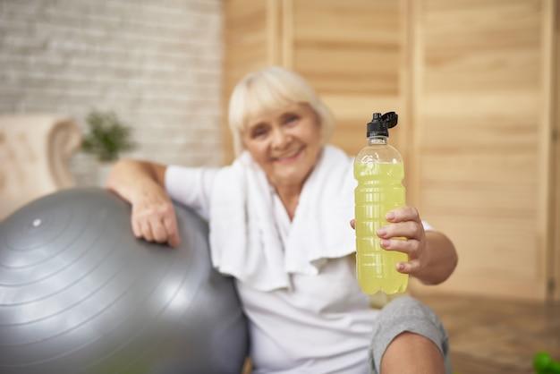 Señora mayor tiene agua de desintoxicación de limón haciendo deporte.