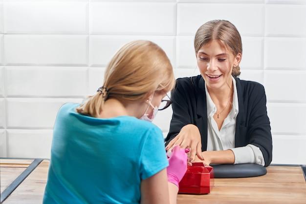 Señora mirando el proceso de hacer la manicura en el salón de belleza para ella.