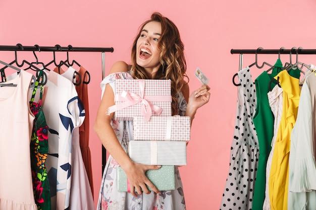Señora moderna con compra de pie en la tienda cerca de perchero y sosteniendo una tarjeta de crédito aislada en rosa