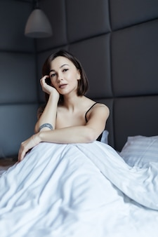 Señora morena sonriente de pelo largo en la cama blanca en luz suave de la mañana debajo del edredón