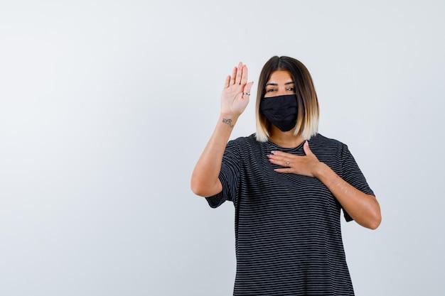 Señora mostrando gesto de parada en vestido negro, máscara médica y aspecto educado. vista frontal.