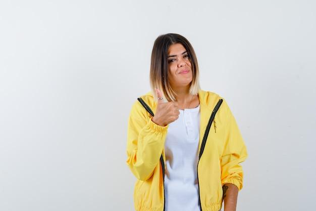 Señora mostrando el pulgar hacia arriba en camiseta, chaqueta y mirando complacido, vista frontal.