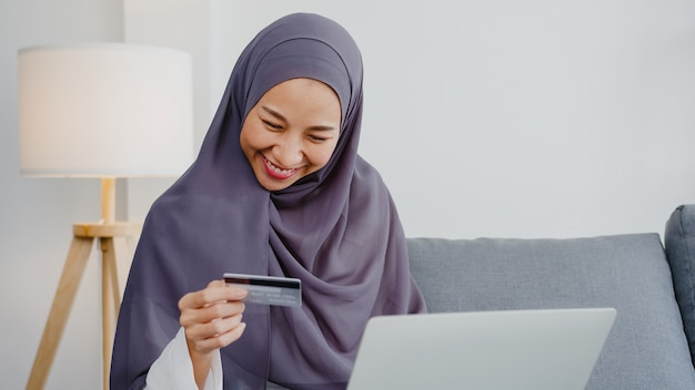 Señora musulmana de asia que usa la computadora portátil, compra con tarjeta de crédito y compra internet de comercio electrónico en la sala de estar de la casa.