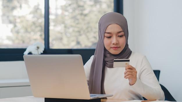 Señora musulmana asiática que usa la computadora portátil, compra con tarjeta de crédito y compra internet de comercio electrónico en la oficina.