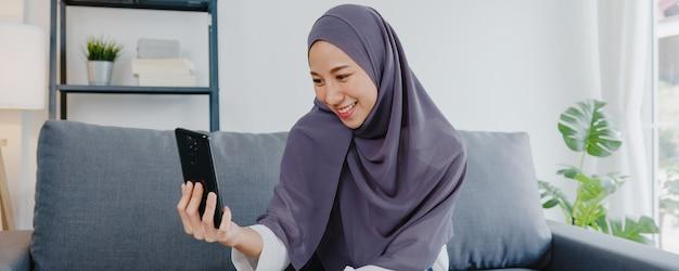 Señora musulmana usa hijab usando videollamada telefónica hablando con pareja en casa.