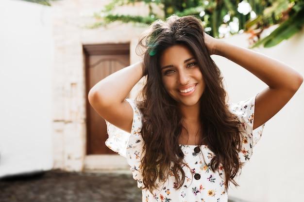Señora de muy buen humor sonríe sinceramente y disfruta de un día soleado de verano contra la pared del edificio blanco y árboles verdes