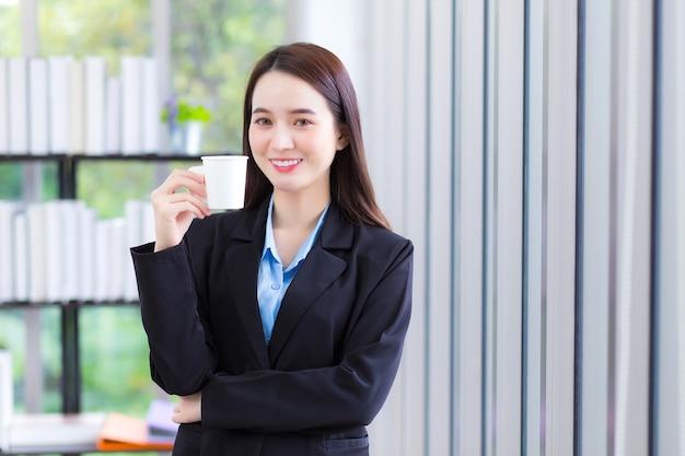 Señora de negocios asiática que viste camisa azul y traje negro sostiene una taza de café en la mano y sonríe