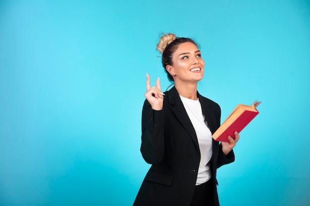 Señora de negocios en chaqueta negra con un pensamiento de libro rojo.