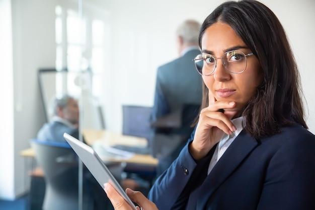 Señora de negocios confiada en gafas y traje sosteniendo la tableta, tocando la barbilla y mirando a la cámara. dos hombres de negocios trabajando detrás de una pared de cristal. copie el espacio. concepto de comunicación