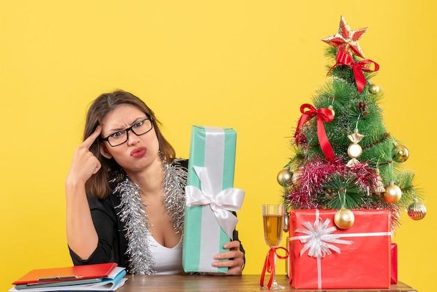 Señora de negocios confundida en traje con gafas mostrando su regalo y sentada en una mesa con un árbol de navidad en la oficina