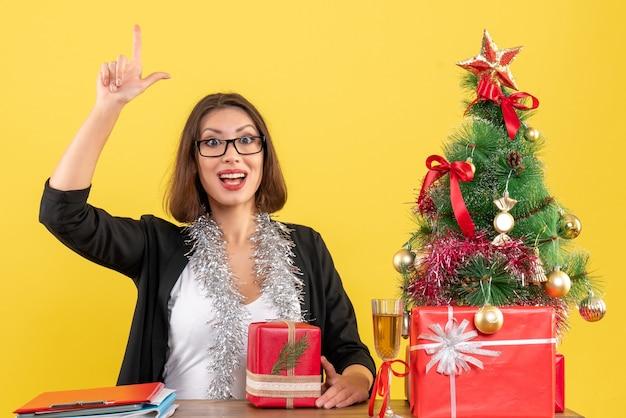 Señora de negocios curiosa en traje con gafas sosteniendo su regalo y sentada en una mesa con un árbol de navidad en la oficina