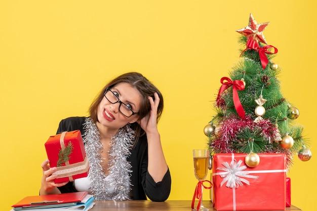 Señora de negocios desconcertada en traje con gafas mostrando su regalo y sentada en una mesa con un árbol de navidad en la oficina