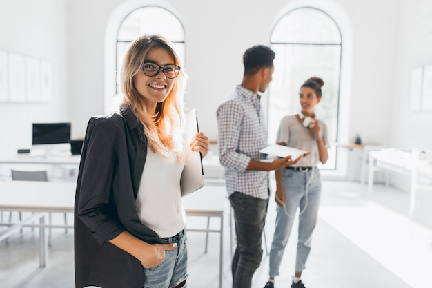 Señora de negocios elegante en chaqueta negra de moda sosteniendo portátil y sonriendo. retrato de secretaria rubia alegre y oficinista africano alto.