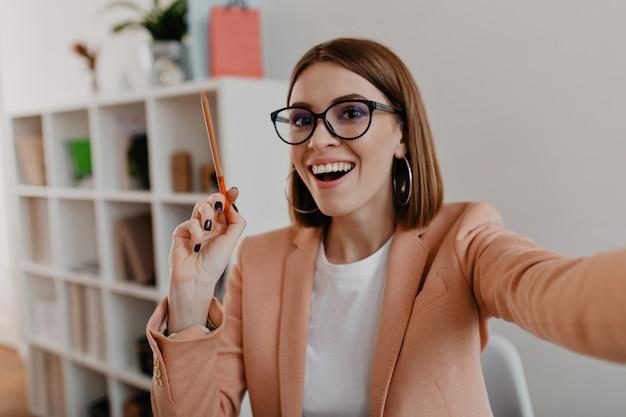 Señora de negocios con gafas y elegante traje ligero hace selfie, sosteniendo un lápiz naranja en sus manos.