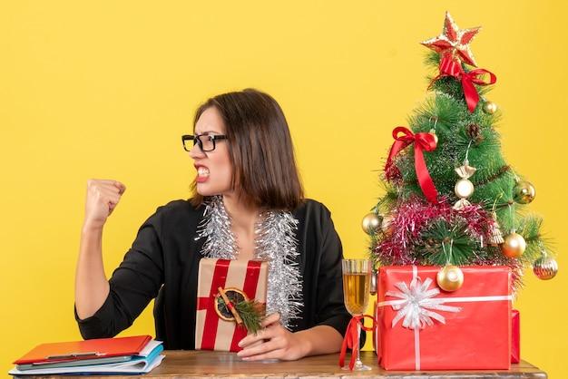 Señora de negocios orgullosa en traje con gafas sosteniendo su regalo y sentada en una mesa con un árbol de navidad en la oficina