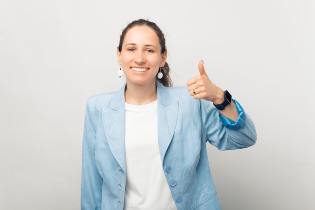 Señora de negocios sonriente joven está mostrando el pulgar hacia arriba en la cámara.