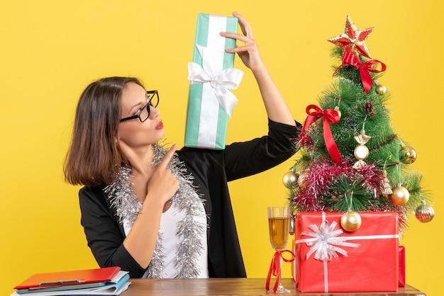 Señora de negocios sonriente en traje con gafas apuntando su regalo y sentado en una mesa con un árbol de navidad en la oficina